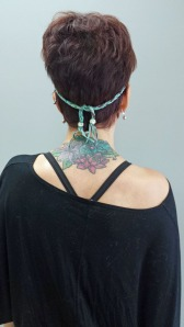 Back view of Michelle with a braided headband with two beads at each end.
